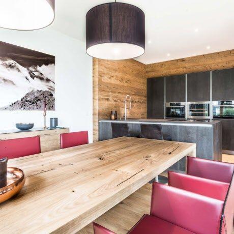 Stimmungsvolles alpinchalet mit einer intuo küche mit keramikfronten und feinen lederstühlen als rote farbtupfer