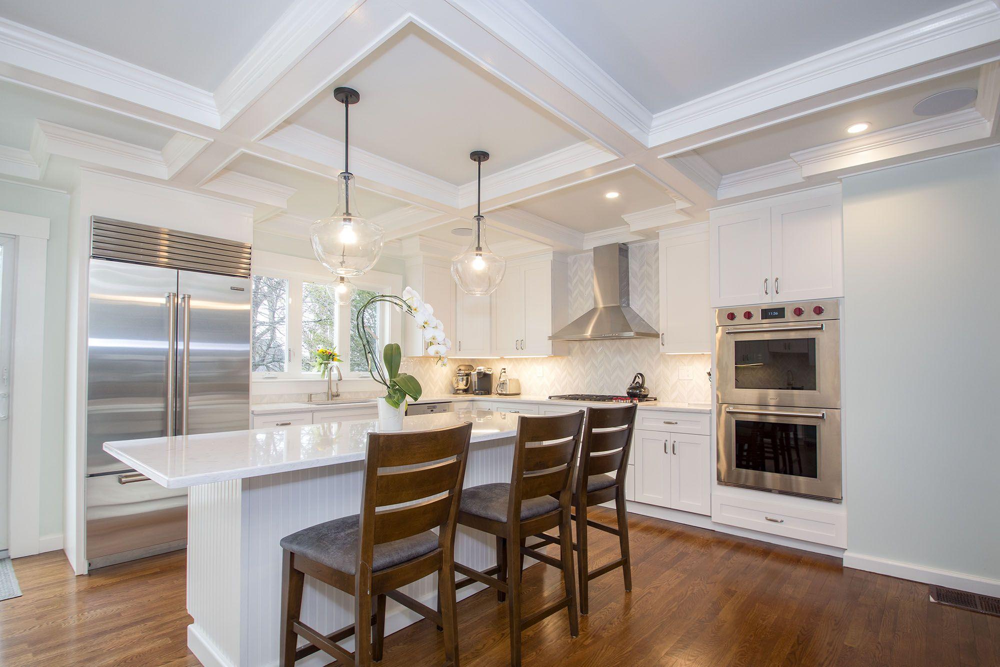 white cabinets, hardwood floors, pendant lights, stainless ...
