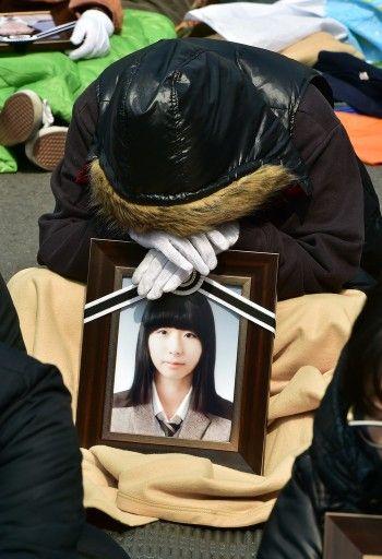 韓国ソウル(Seoul)の大統領府(青瓦台、Blue House)前で行われた旅客船セウォル(Sewol)号沈没事故での抗議集会に、犠牲となった生徒の写真を手に参加する遺族(2014年5月9日撮影)。(c)AFP=時事/AFPBB News