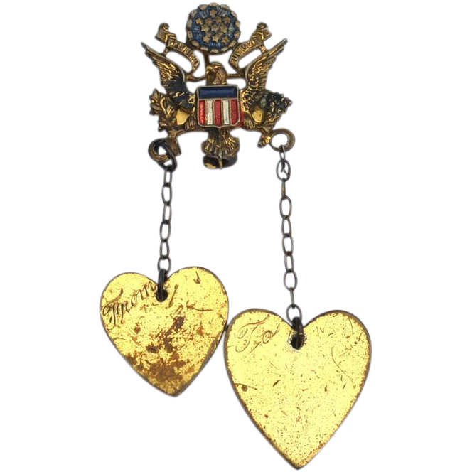 This is a fabulous and early pin which was made by Coro during WWII.  This sweetheart pin is made of gold toned metal and features two dangling hearts