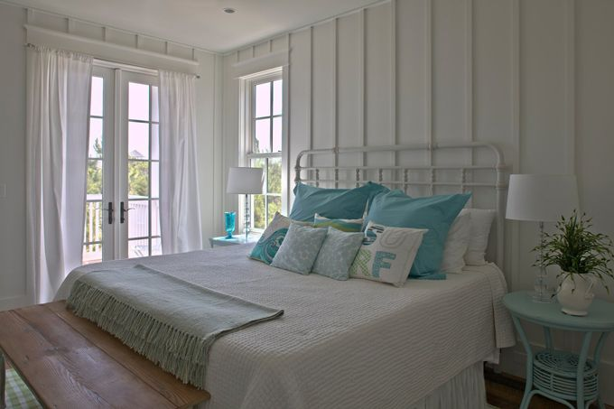 Geoff Chick & Associates white iron bed & bedding - round turquoise wicker night stand - pine bench & checked rug - cottage fresh