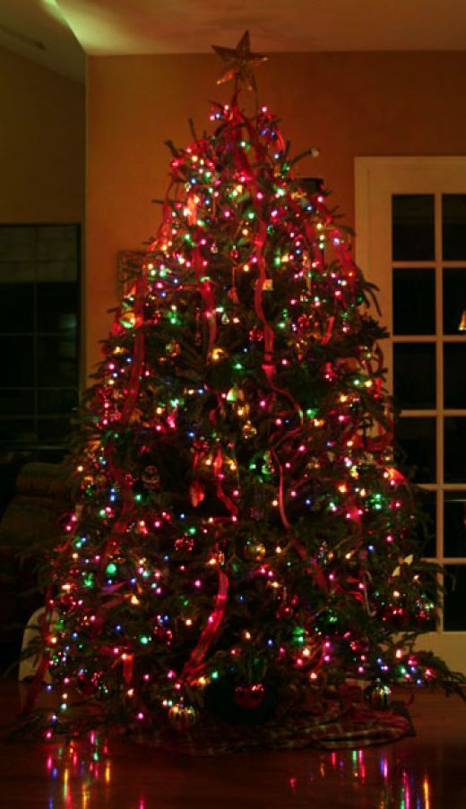 christmas tree decorated in multi colored lights multi colored mini christmas tree lights with red ribbon decorations
