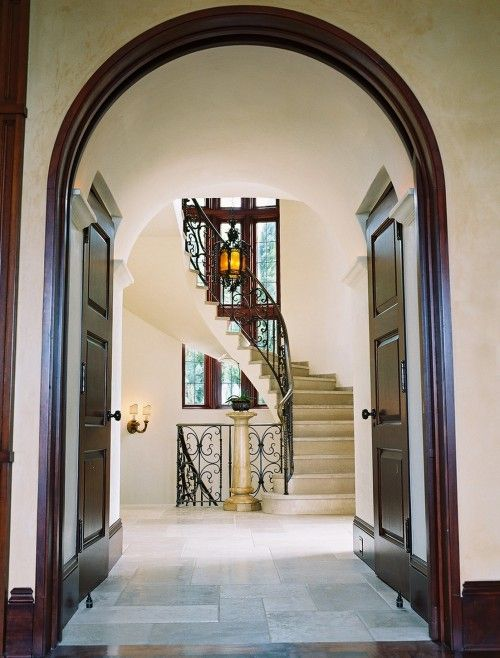 Dark Wood Paired With Travertine Floors And Iron Scrolls Arch And