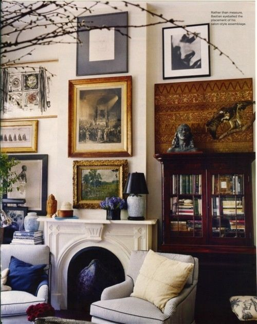 gallery wall, modern art sculpture photography, blue and white, fireplace, mantle, comfy chairs, blue piping, antique secretary, indoor branches, English drawing room