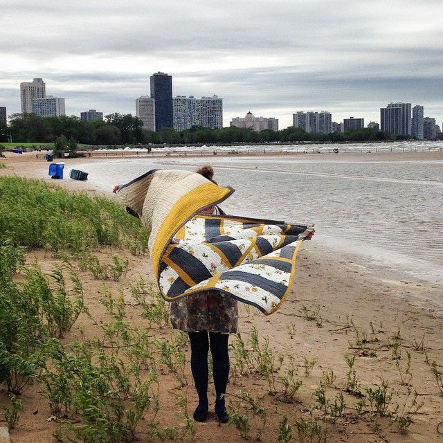 Artist Heidi Parkes at Montrose Beach in Chicago with her quilt, 'Flower Fence.' #quilt #handquilted