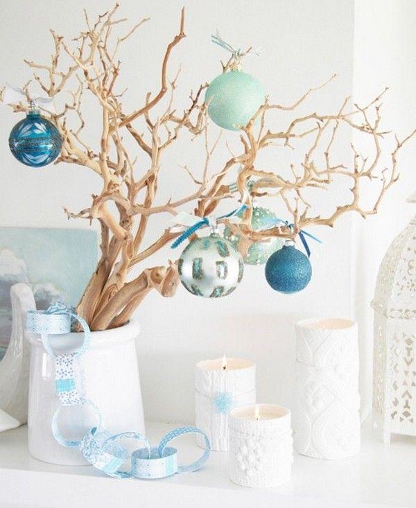 branches en vase blanc décorées de boules de Noël bleues