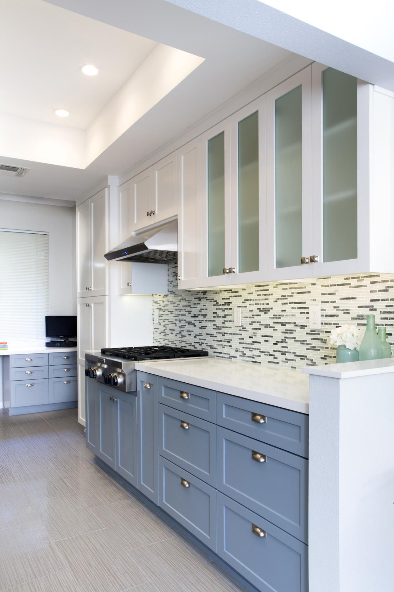 this gray and white kitchen features two cabinet colors and a striking glass tile backspla on kitchen cabinets grey and white id=56197