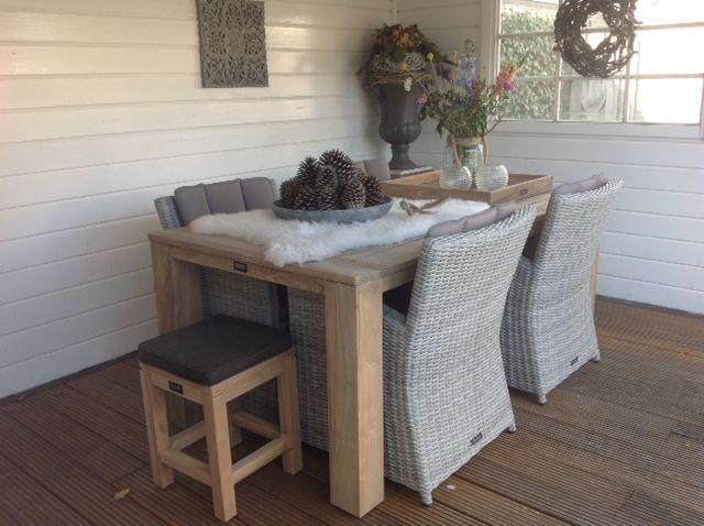 Gezellige tuinset met houten tafel en gevlochten stoelen tuinset