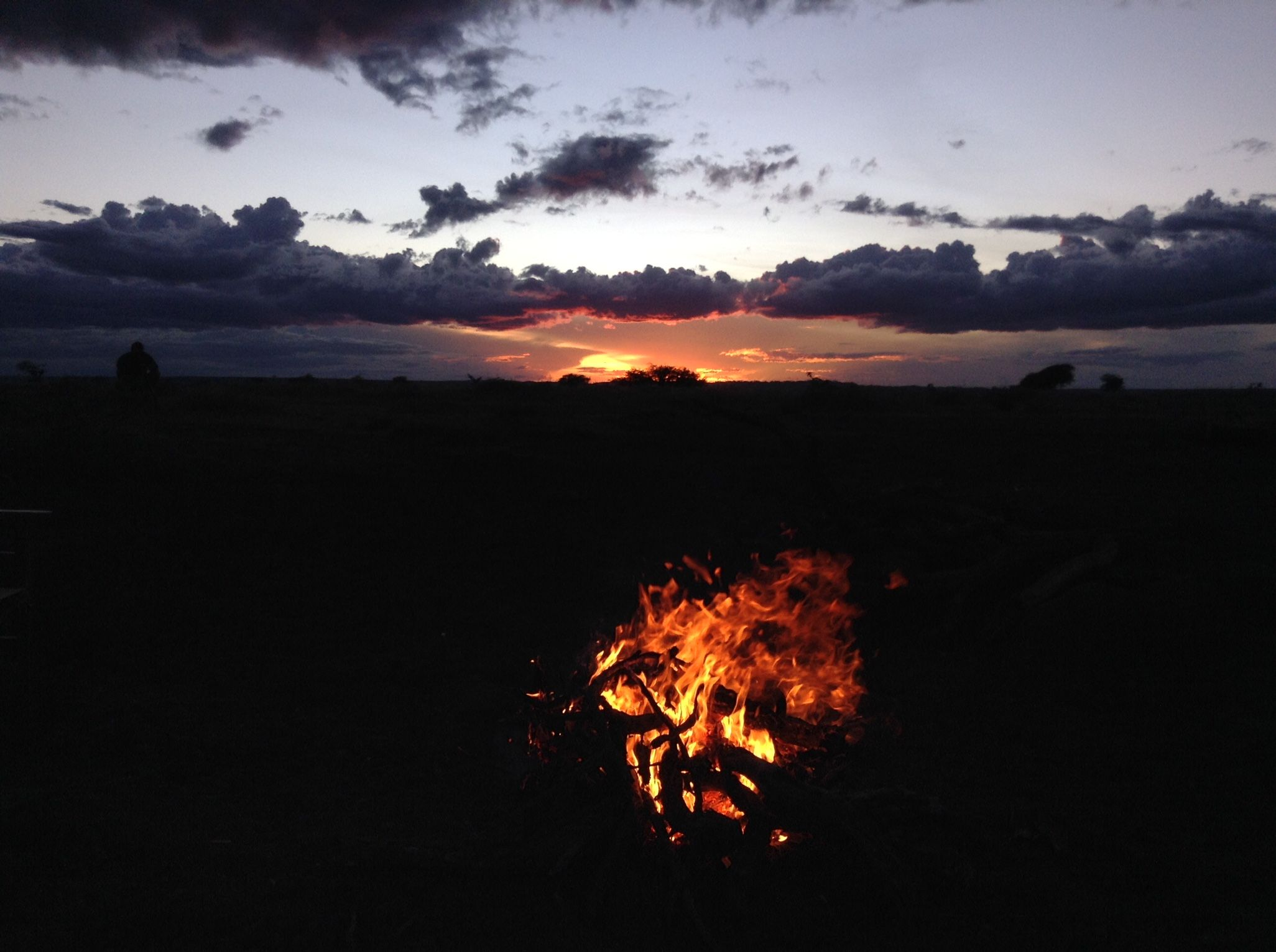 Watching the fire while having Sundowners on the plains