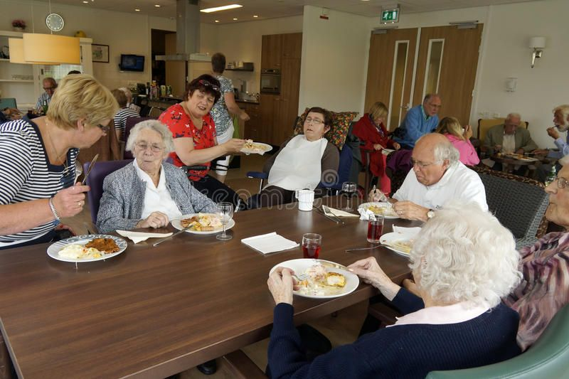 Old people in a nursing home having dinner With caretakers in a homely environm