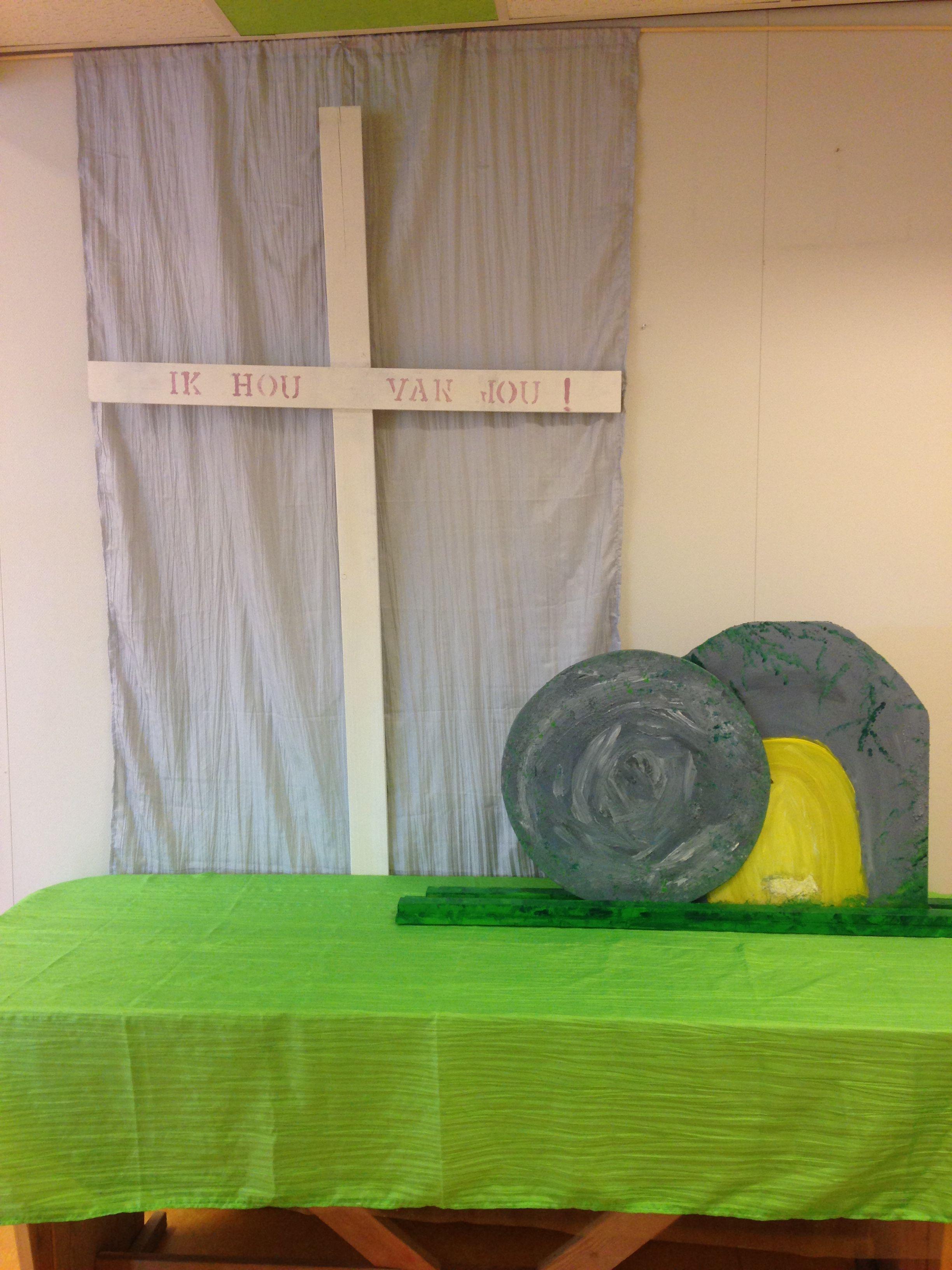 Pasen: het kruis waaraan Jezus stierf, maar waaruit Zijn liefde voor ons blijkt. Ik hou van jou! Jezus is opgestaan, het graf is leeg!  De steen is draaibaar. Wanneer de steen weggedraaid wordt, zie je dat het graf leeg is; Jezus is opgestaan. In het midden van de steen zit een boutje + moertje. Op het graf , ter hoogte van het midden van de steen, zit een horizontale gleuf waar de bout / moer + wiel doorheen/ achterlangs glijdt. Materiaal: MDF, acrylverf met steentjes erdoorheen , latjes…