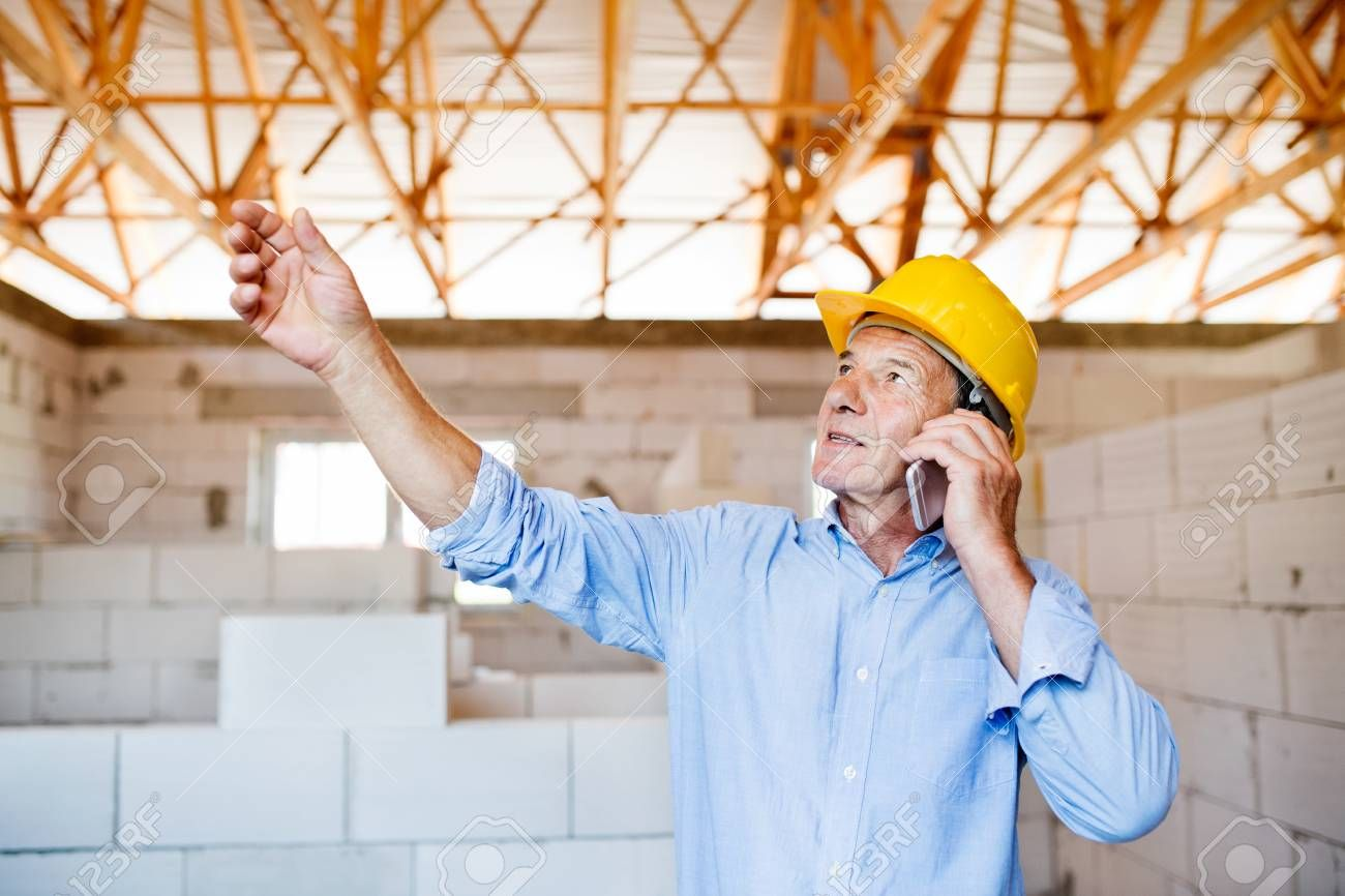 Senior architect with smartphone at the construction site