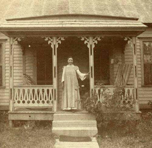 """Laura Ingalls Wilder on the front porch of the home Almanzo built for them near Mansfield, Missouri -- author of """"Little House on the Prairie"""" series of children's novels based on her childhood in a settler family."""
