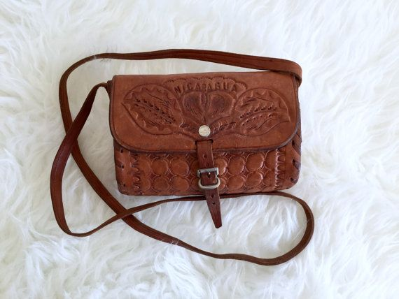 Thick Tooled Leather Bag / Small Tooled Nicaraguan Cognac Shoulder Evening Purse / Brown Leather Boho Hippie Foldover Handbag w Buckle Super beautiful and strong vintage Nicaraguan tooled brown leather handbag Shoulder strap Fold over with buckle Holds the essentials for a night/day out! (cell phone, wallet, keys, lip stick, mascara) Will last a lifetime  Measures: 6 wide 4.25 tall 2.25 deep strap is 40 long total, .5 wide strap   CONDITION REFERENCE CHART RATING: Excellent Bag is in…