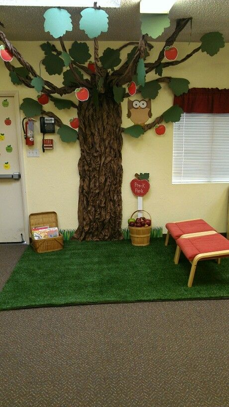 Classroom reading area, we call it THE PRE-K PARK! We made a tree from butcher paper, got a company to donate a slab of artificial turf, and got a few benches from the thrift store. We also used a picnic basket to put some books in for the start of school Apple theme.