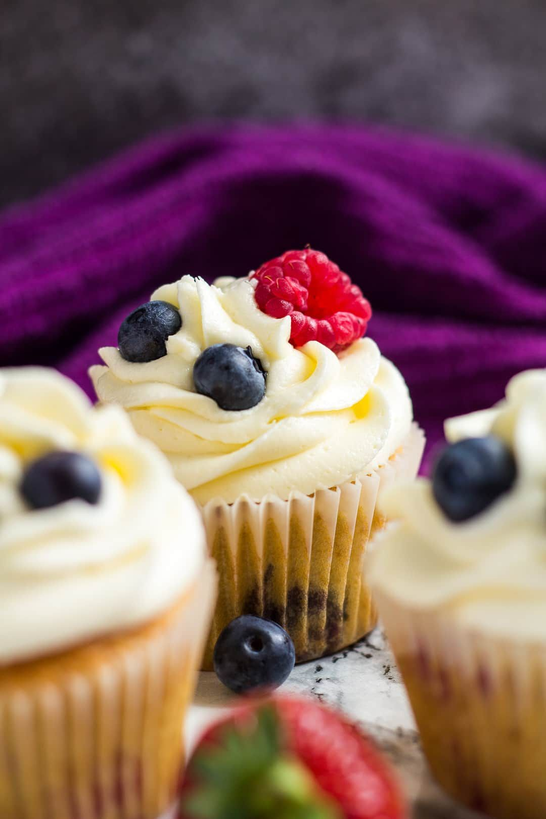 Summer Berry Cupcakes- Deliciously moist and fluffy vanilla cupcakes stuffed with summer berries, and topped with a sweet buttercream frosting!