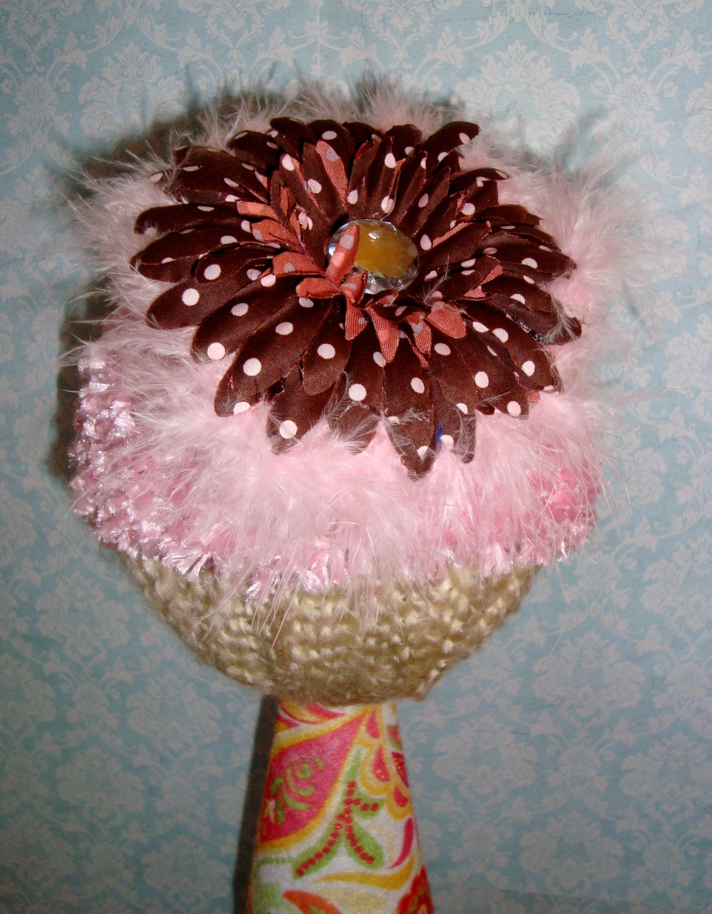 Fuzzy pink waffle hat with brown and pink polka dot flower.