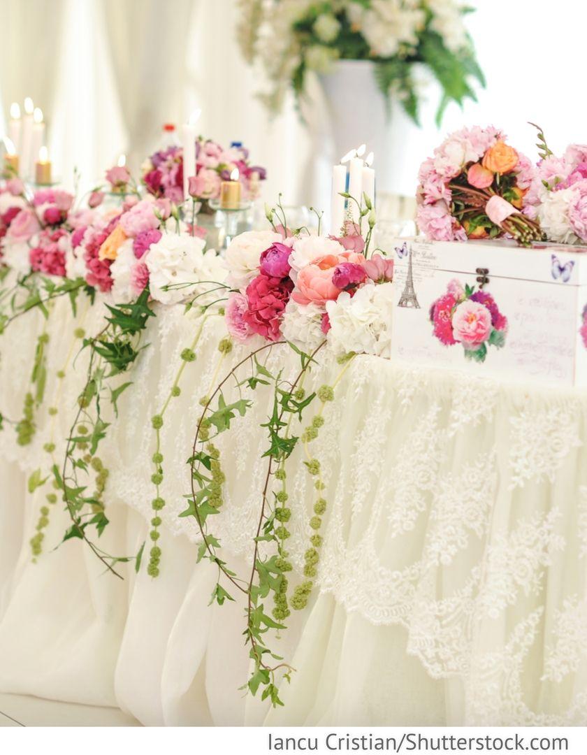 Dekoration mit Blumen und Stoff des Brautpaartisches für