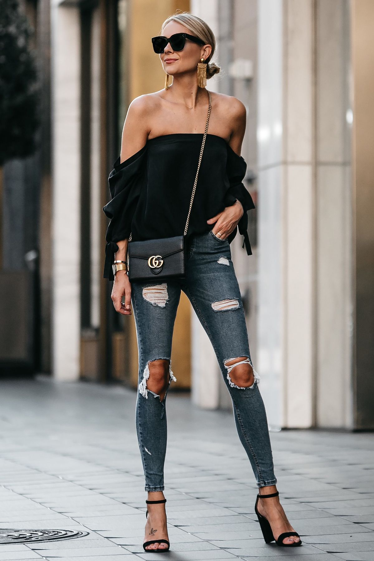 190ed2cfa1554 Blonde Woman Wearing Club Monaco Black Off-the-Shoulder Top Denim Ripped  Skinny Jeans Outfit Black Ankle Strap Heels Gucci Marmont Handbag
