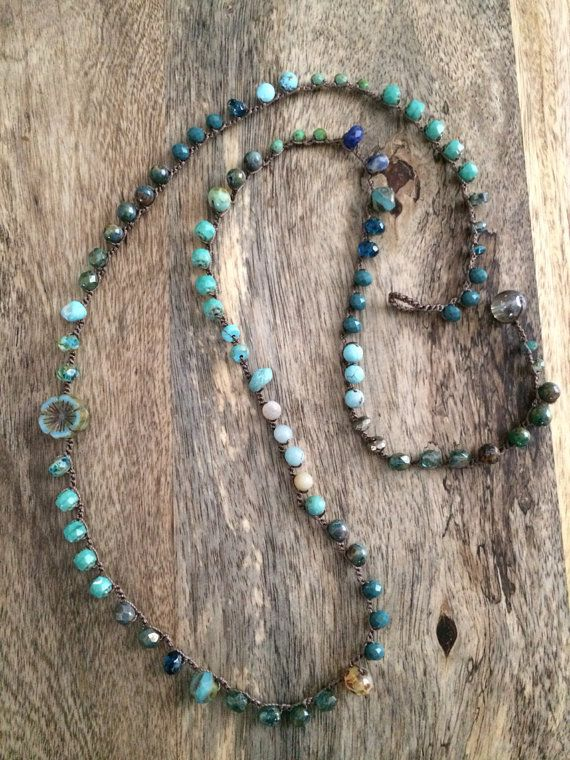"""Edgy and chic, this crocheted F.Y.A. necklace features a beautiful multicolored arrangement of semi precious stones and quality czech beads all featuring blue, turquoise, green beach hues. The stones are hand crocheted and secured throughout a light brown nylon cord.  Measures 33.5"""" for an awesome layering look."""