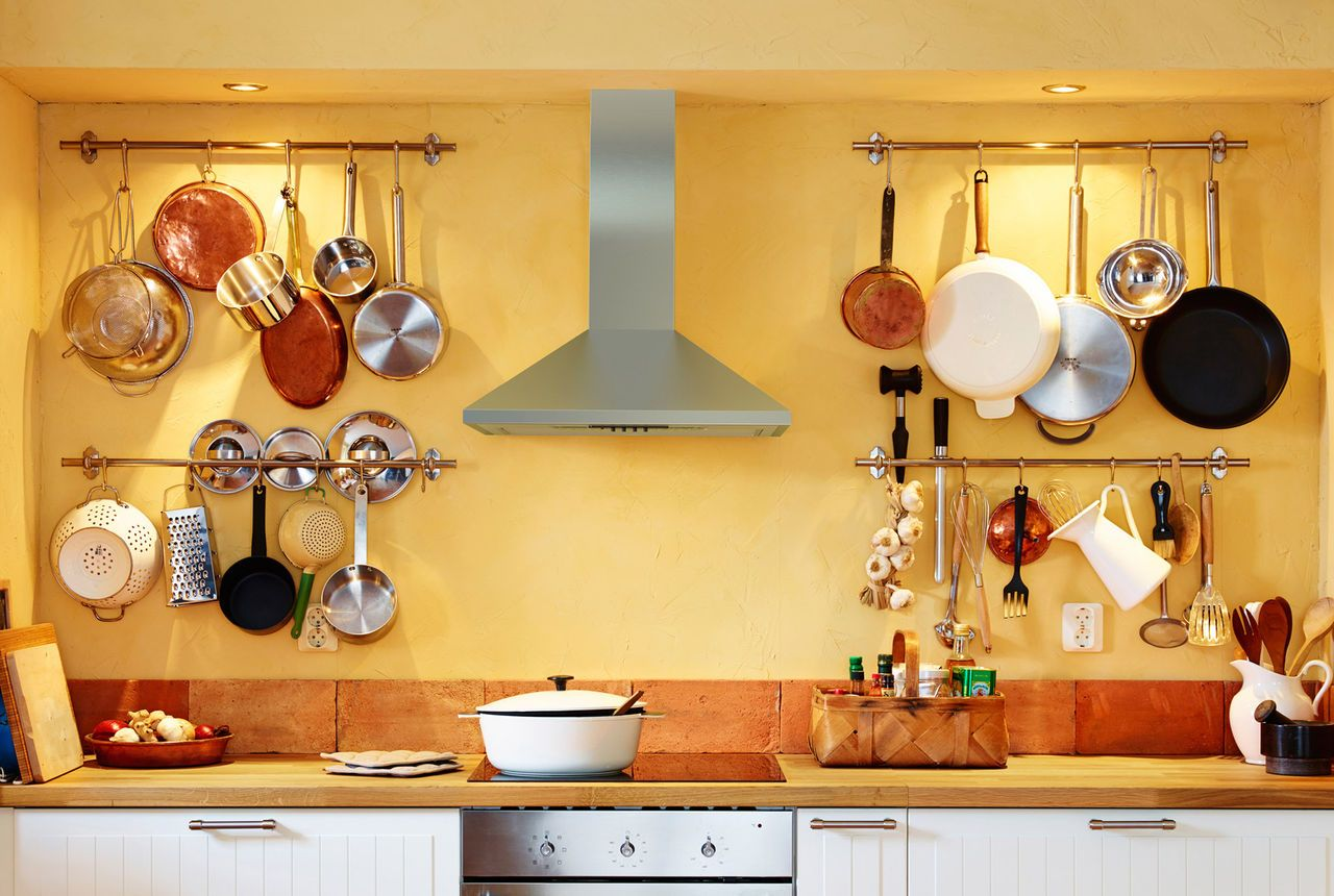 IKEA hob and hood. Four wall-mounted rails holding lots of cookware ...