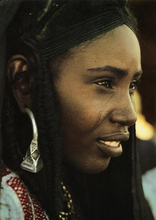 Africa | A woman of the Ullimeden Tuareg wears tsabit earings with a pyramid shaped terminal knob. These intricately decorated earrings of solid silver are an obvious mark of wealth. Middle Niger. | ©Angela Fisher, Africa Adorned, 1984