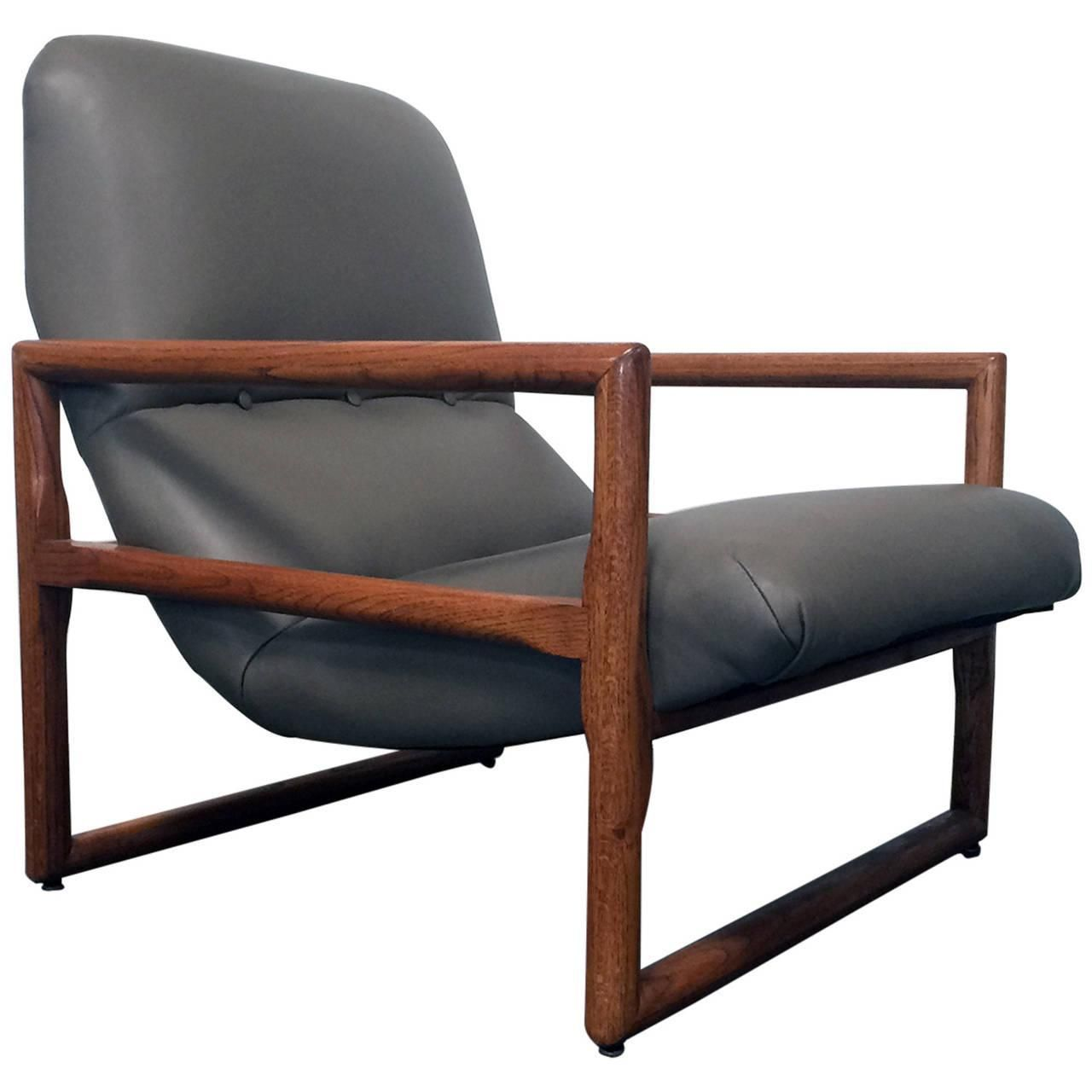 "Milo Baughman ""Cube"" Arm Chair . Finished with grey leather and an oak frame. Originally designed in 1948 this chair speaks to a distinct moment in modern design. This would be wonderful in any room of your home or office!"