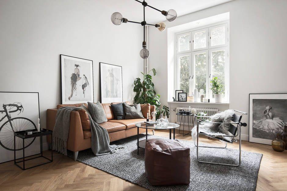 Grey Scandinavian living room with a tan leather sofa