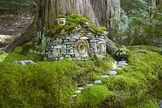 Stone house at the base of a tree with stone walkway and ...
