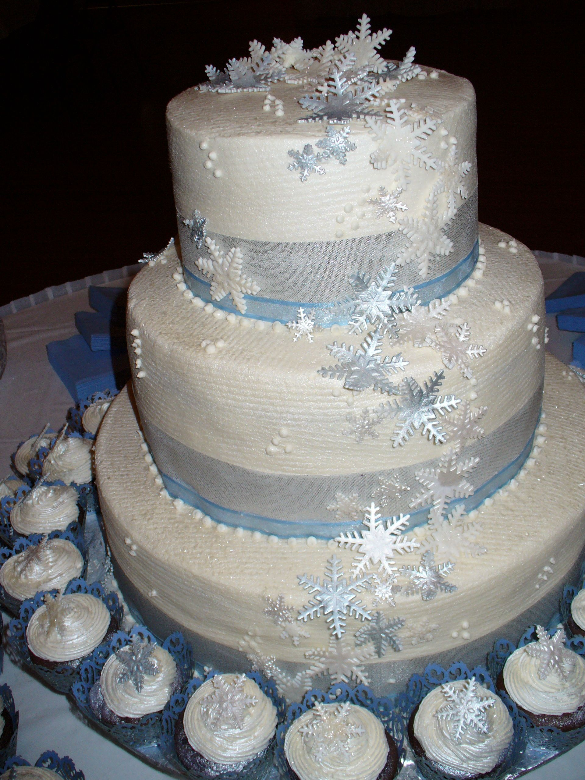 silver and blue snowflake wedding cake with cupcakes