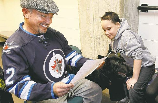 Dog Whisperer Cesar Millan reads Cole Hein's famous lick-it list in an MTS  Centre locker room on Sunday. Millan was so touched by Cole's actions he is  creating a legacy fund in the name of Cole's beloved dog, Bingo. Bingo died in September.