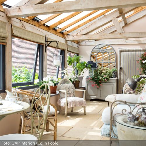 Gemütliche Gartenmöbel im romantischen Wintergarten (mit
