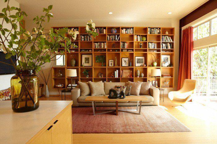 buecherregal wohnzimmer aus hellem holz hinter beige sofa - wohnzimmer orange beige