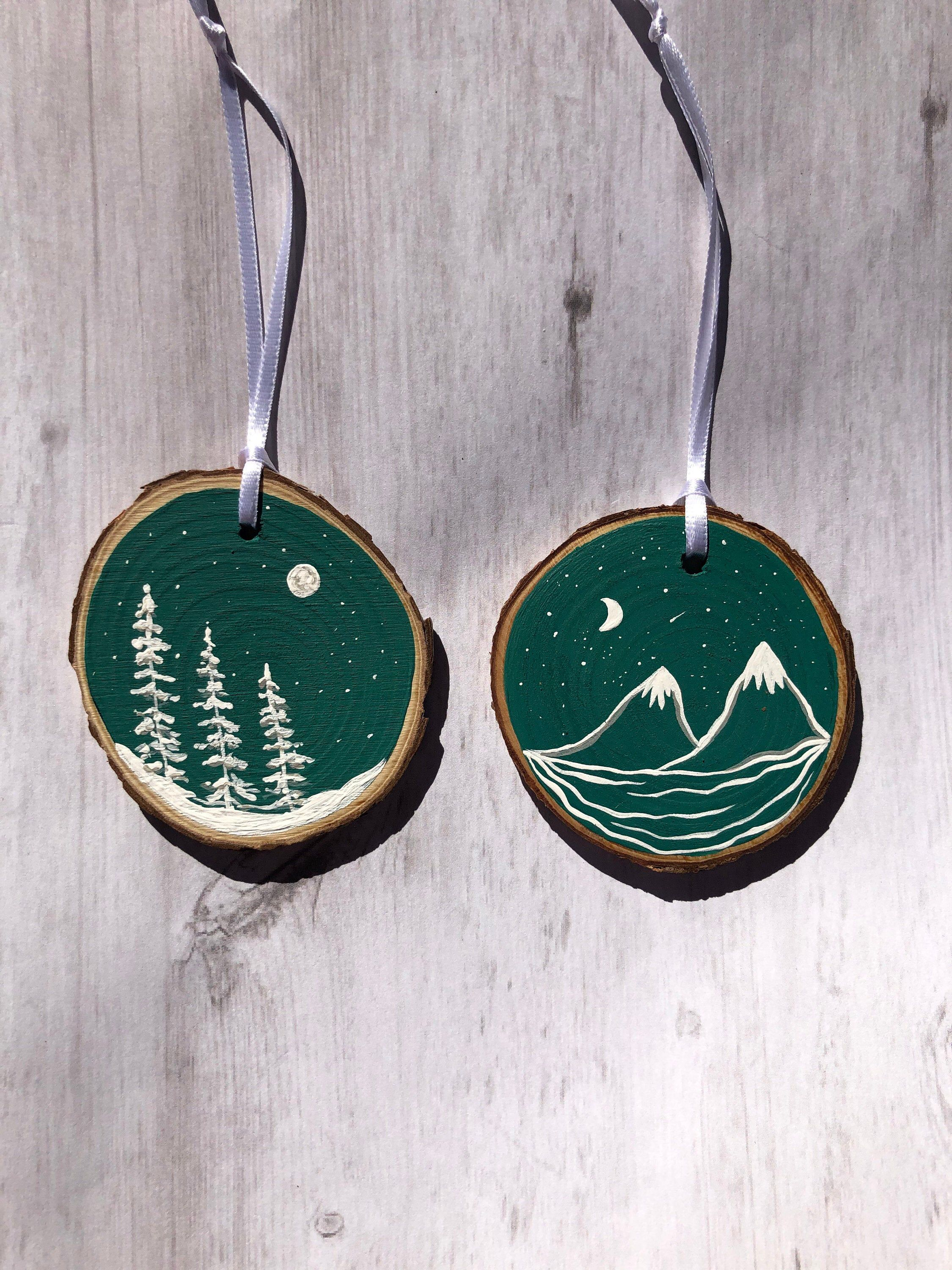 Photo of Set of two wood slice ornaments , green and white white winter trees , mountains, moon, hand painted