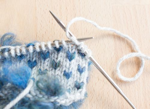 When it's time to add a thrum insert the needle into the stitch and wrap the yarn as normal.