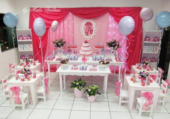 Decoração Barbie e as sapatilhas mágicas, composta por:  Painel de Tecido  Mesa Branca Retangular 2,20x1,10  Mesa Retangular 1,50x0,60  4 Jogos de mesa 60x60 c/ 4 cadeiras cada, ornamentada com laço e sapatilha  Ornamentação com Flores Naturais 2 Porta doces  4 Vasos de porcelana com flores naturais  4 Vasos de plástico nas mesinhas, com flores naturais  Iluminação de led painel  2 Armários brancos  2 Vasos de Cerâmica Rosa no chão com flores naturais  3 bonecas Barbie e as Sapatilhas…