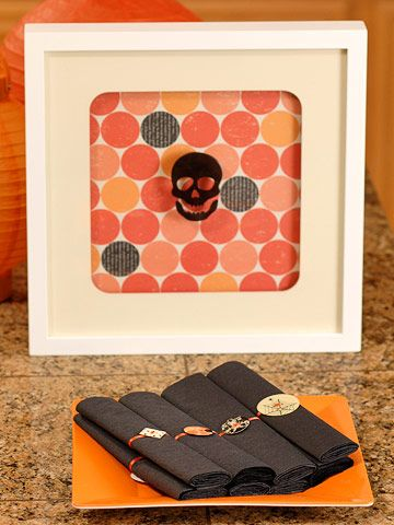 For easy and inexpensive party decor accents, fill black, white, or silver frames with the same scrapbooking paper used on your table. Adorn the outside of the frame's glass panel with Halloween window gels, such as the black skull shown here.