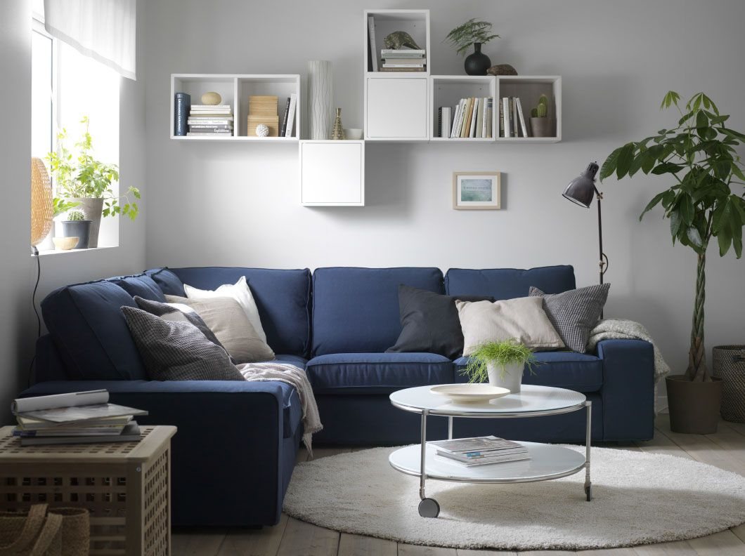 Woonkamer met blauwe hoekzitbank gevuld met extra kussens in beige