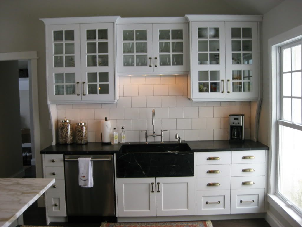 Black countertop and apron sink white cabinets with hardware bright