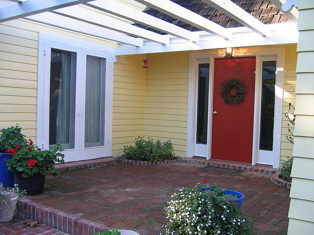 yellow house w/ white trim, green shutters and porch floor & red