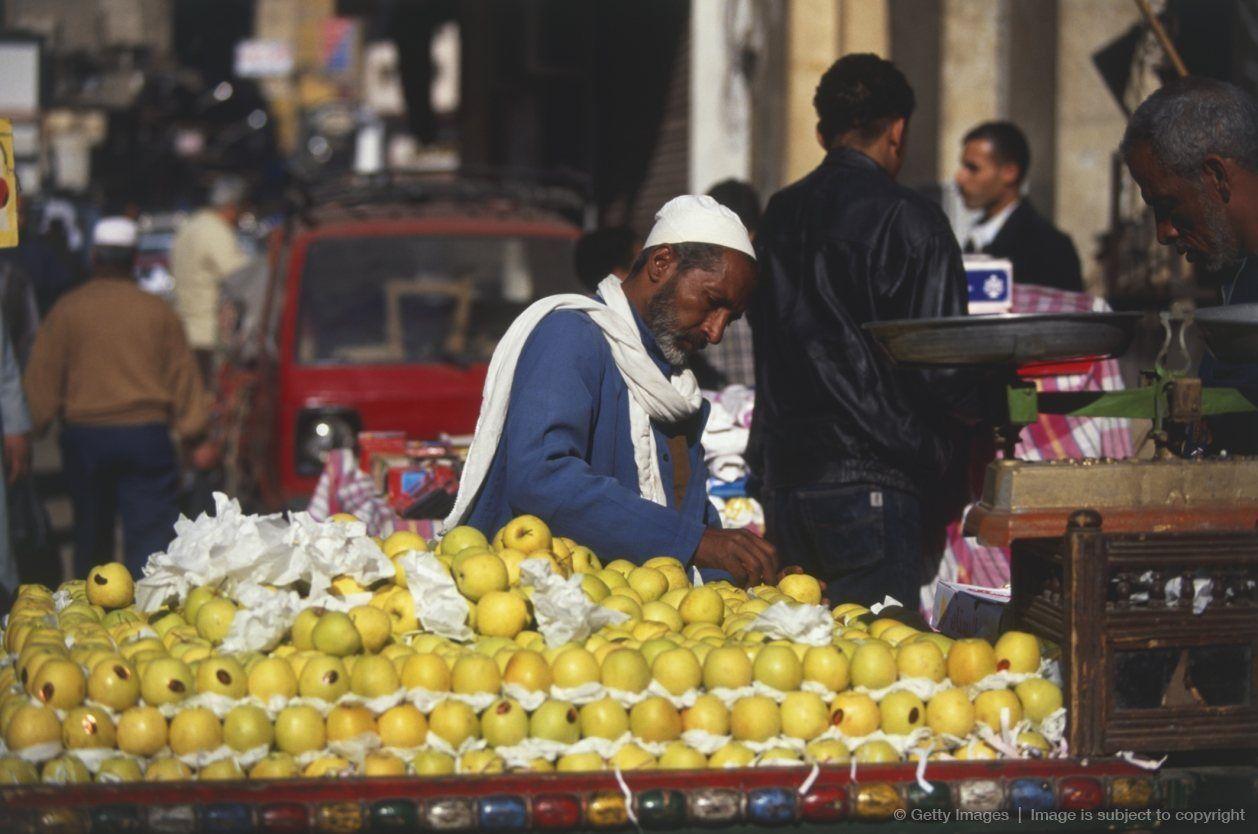 Africa, Egypt, Cairo, fruit vendor in the bustling street market of Sharia Muski.
