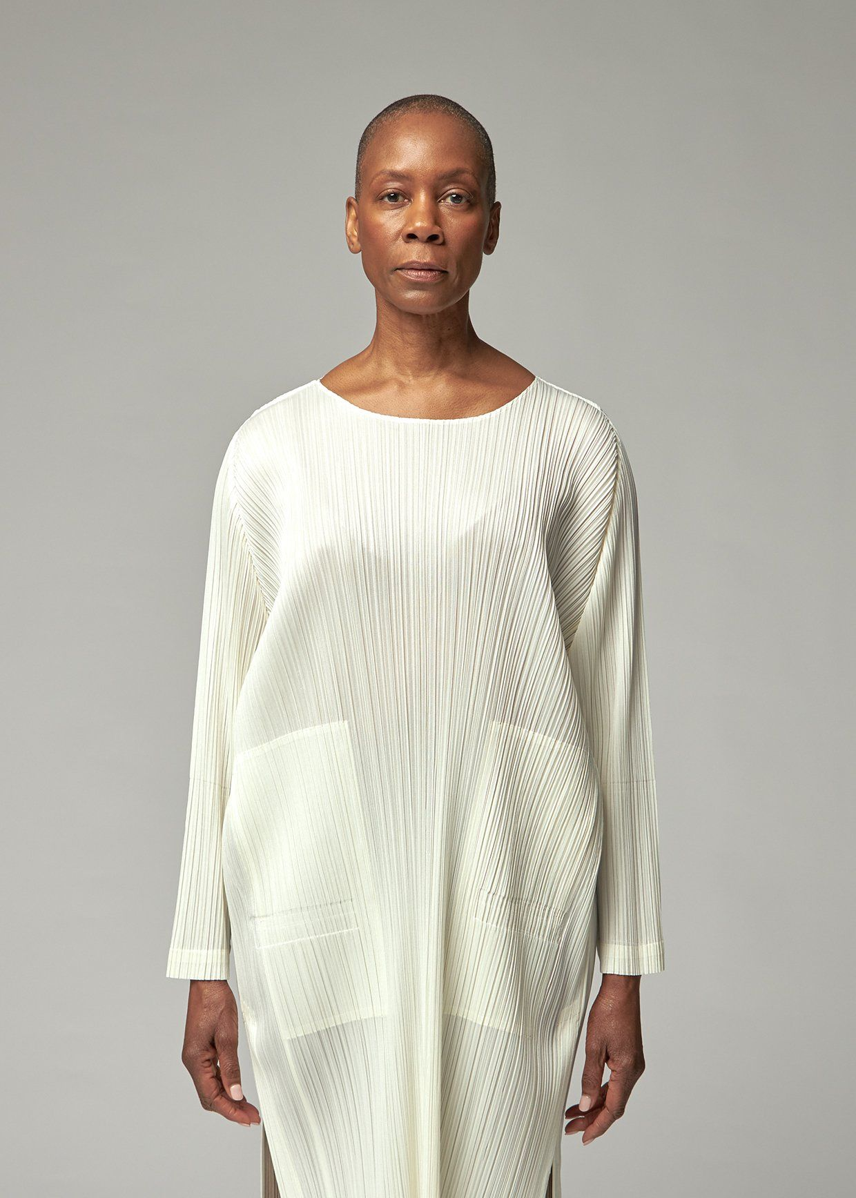 Tunic in signature lightweight vertical pleats with large, square front pockets. Long sleeves. Side slits. Machine wash cold in net. 100% polyester. Made in Japan. | PLEATS PLEASE ISSEY MIYAKE Women's Long Sleeve Tunic Top in Off White Size 3