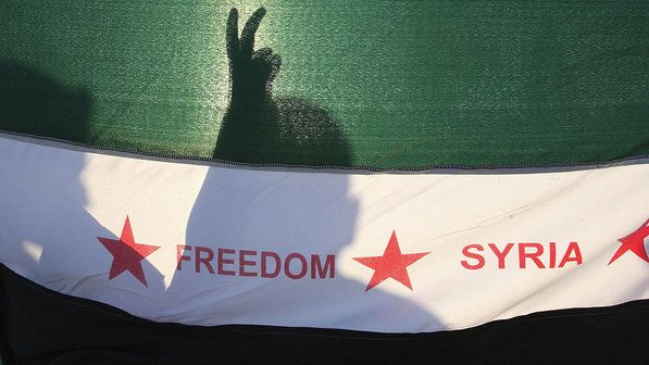Manifestantes com bandeira da oposição síria durante uma manifestação contra o presidente, Bashar Al-Assad em frente à embaixada da Síria, em Amã