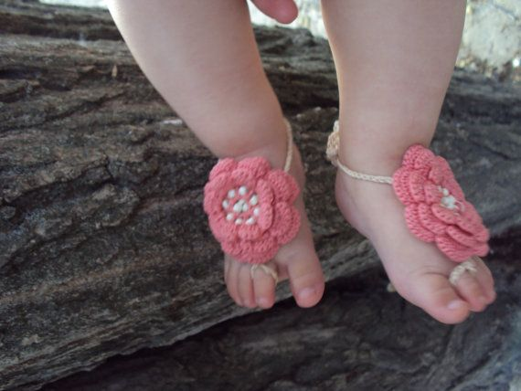 These whimsical crocheted Barefoot Baby Sandals are shown using 100% cotton coral yarn. The center of the flower is decorated with beads.   Baby sandals are worn by placing a loop around the second toe of baby's foot and tied around the ankle. The straps can be tied in the back by the heel, or wrapped around and tied on the side of the foot.   These will fit most babies 0-12 months, depending on foot size.   Custom colors available.