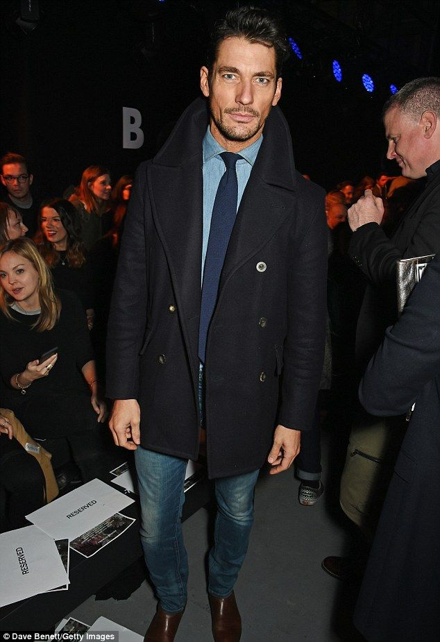 Pouting: Supermodel David Gandy stormed the front row looking incredibly suave in a navy pea coat with stone washed jeans and a blue shirt