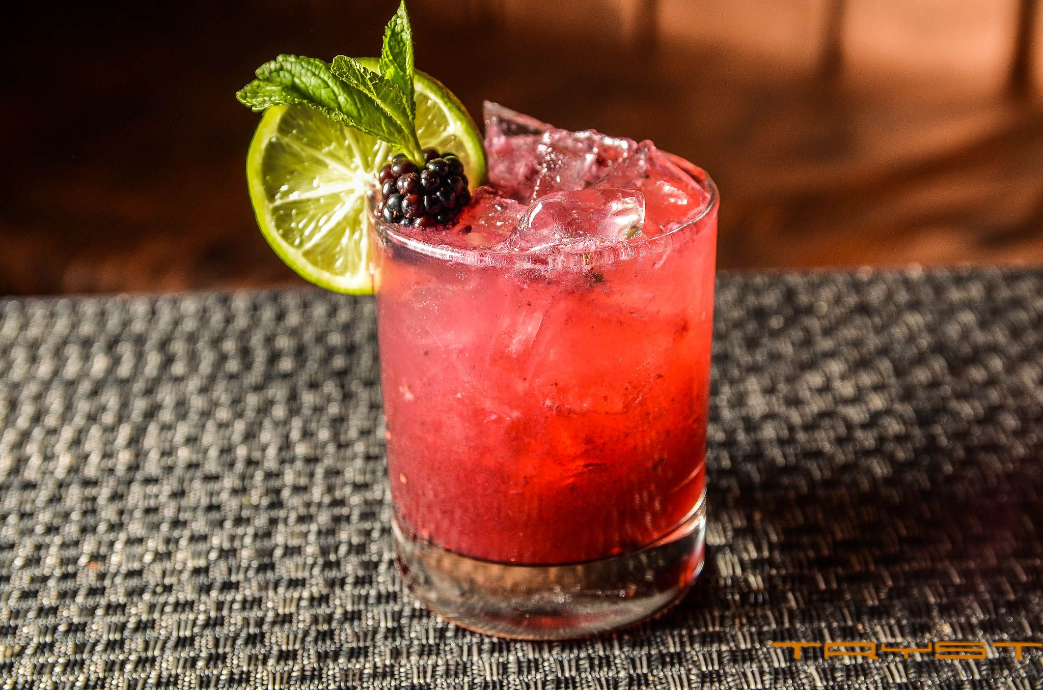 Tryst Bramble - a fragrant blend of muddled blackberries and mint with Nolets gin and a splash of lemon juice, then topped with champagne and served over ice.