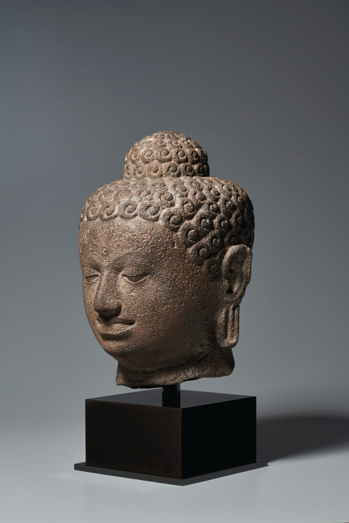 AN ANDESITE HEAD OF BUDDHA | INDONESIA, CENTRAL JAVA, 9TH-10TH CENTURY | Christie's