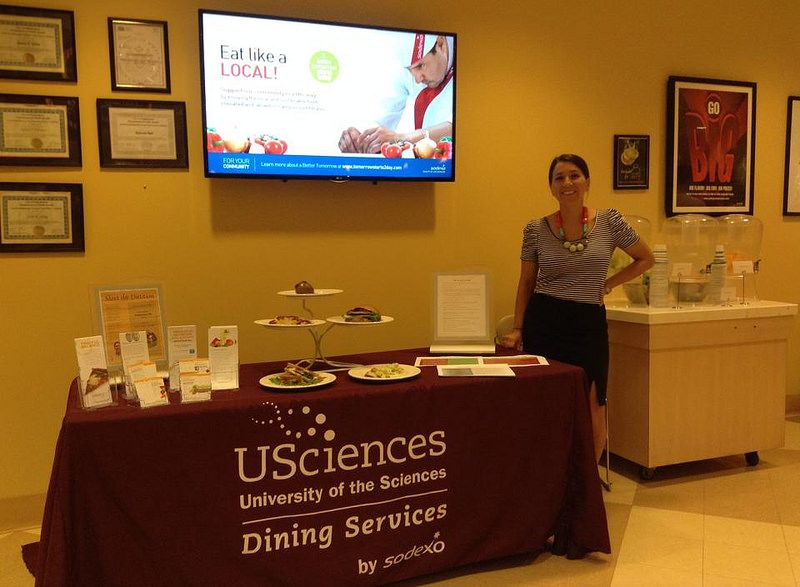 Photo of the Week! Sodexo Registered Dietitian Aliz Holzmann featuring apple-based menu items at University of the Sciences.