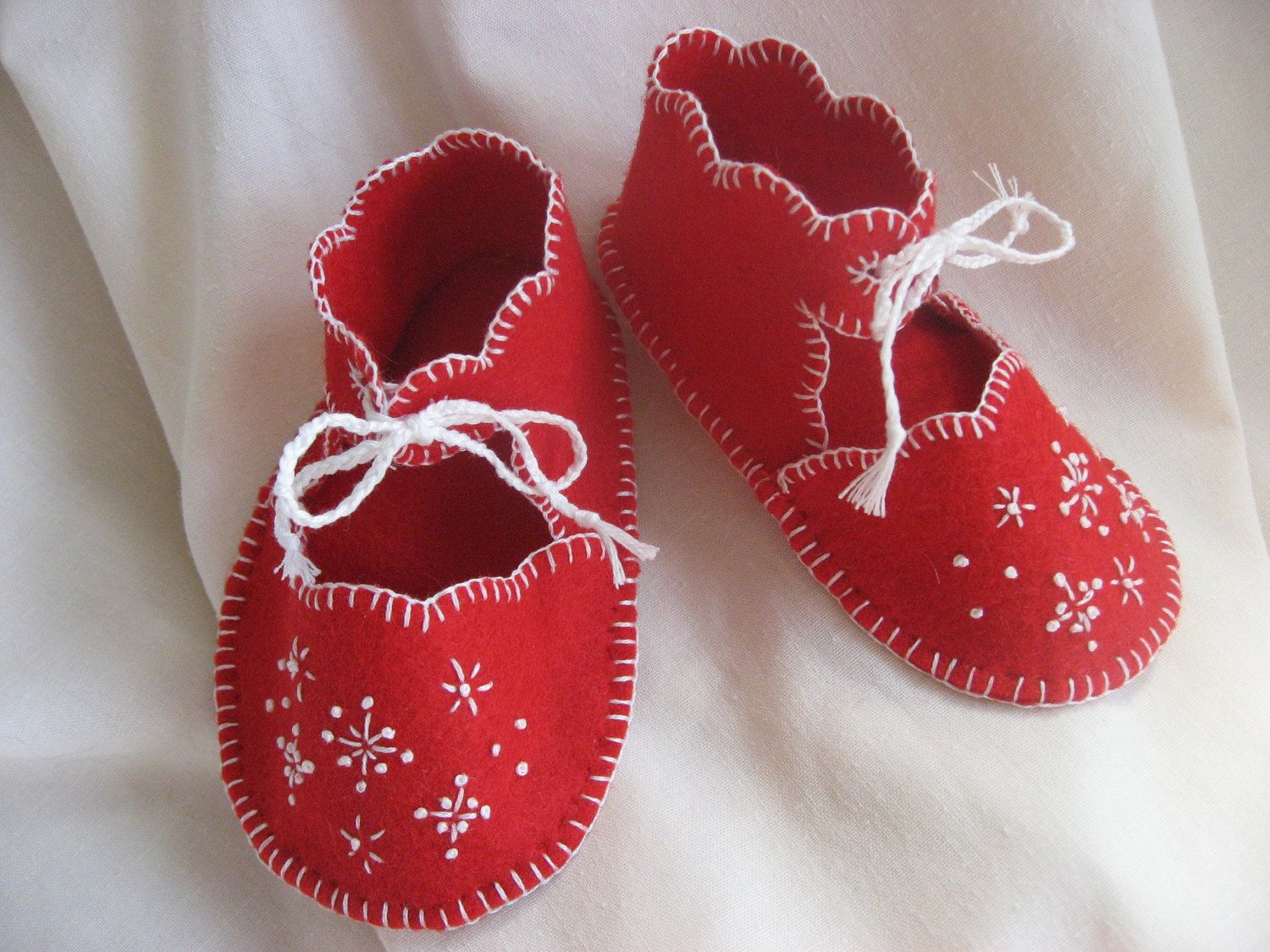 My mom made these!! Handmade wool-blend felt booties with snowflake embroidery. $17.95, via Etsy.