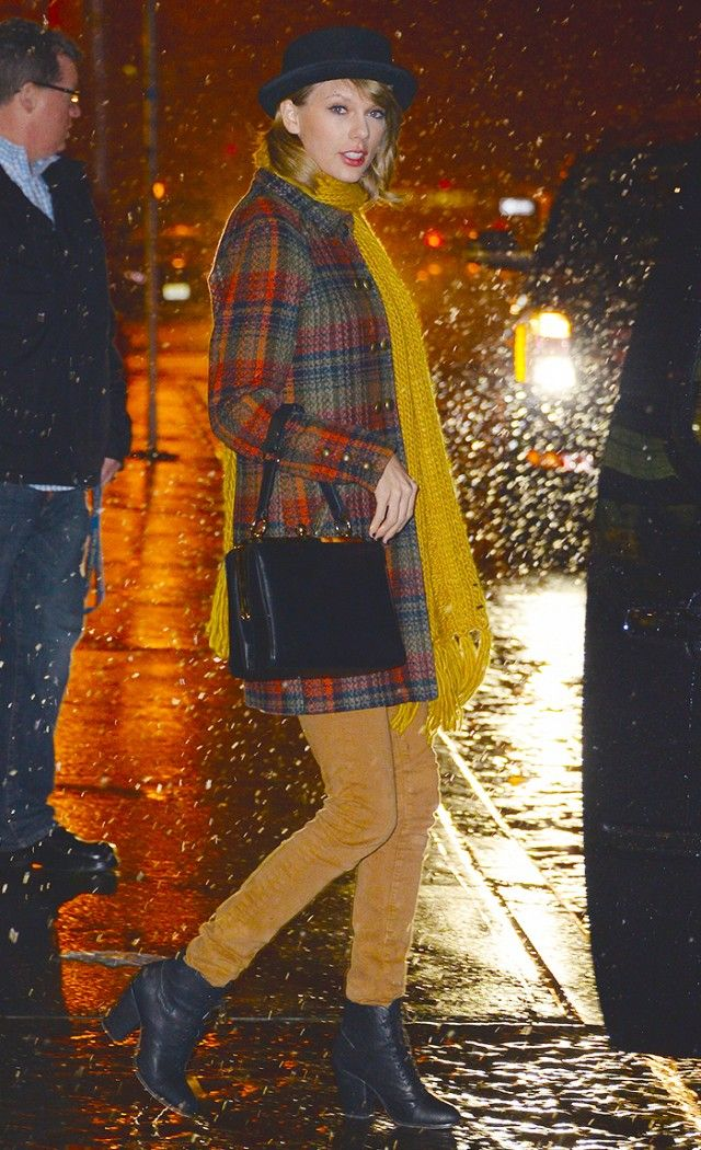 Taylor Swift wears a classic plaid coat with a bright yellow scarf and sleek ankle boots on a rainy NYC night